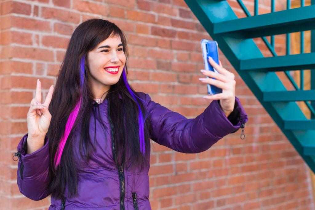 pretty-girl-with-long-coloured-hair-takes-a-selfie-LUKVXPK